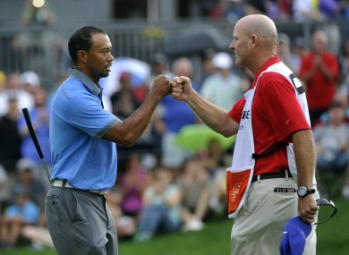 Tiger Woods fist bumps with his caddy, Joe LaCava.