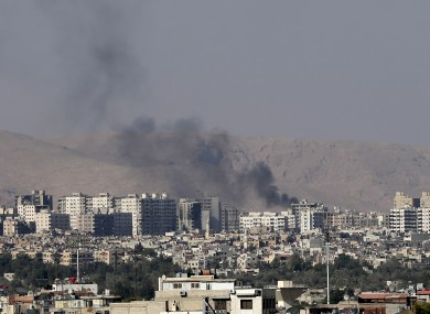 Black columns of smoke from heavy shelling in a Damascus suburb