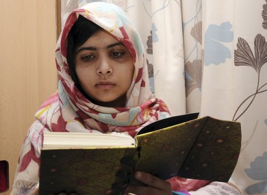 Malala Yousafzai reading a book while in hospital