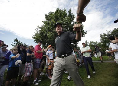 Phil Mickleson fist bumps with a fan on the ninth tee at Oak Hill GC yesterday.