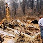 U.S. Senator Jon Tester looks at the remains of a Lolo Creek home. (AP PHOTO)
