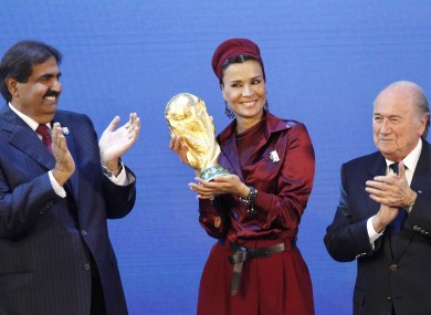 Sheikh Hamad bin Khalifa Al-Thani, Emir of Qatar, left, and Sheika Mozah bint Nasser al-Misned hold the World Cup trophy as FIFA President Joseph Blatter, right, applauds after the announcement of Qatar hosting the Finals.