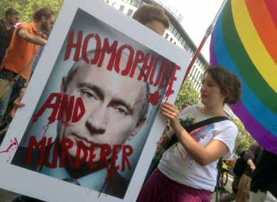 Demonstrators hold a poster with the portrait of Russian President Vladimir Putin during a protest march in Berlin, Germany this August.