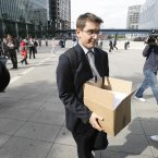 A worker holding a box, leaves the Lehman Brothers headquarters at Canary Wharf in London.<span class=