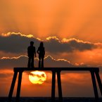 The sun rises over the  giant sculpture of a man and woman situated 300 yards out to sea off the coast of Northumberland at Newbiggin-by-the-Sea.