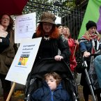 Deirdre McCarthy covers her son Paddy Nevin, 3 years old, from the rain during the protest.<span class=