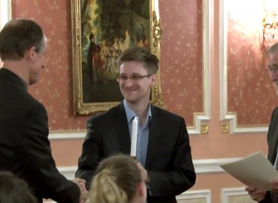 File: Former National Security Agency systems analyst Edward Snowden, center, receives the Sam Adams Award in Moscow