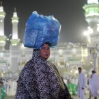 An Muslim pilgrim carries her luggage in front of the Grand Mosque in the holy city of Mecca, Saudi Arabia. The Muslim annual Hajj, or pilgrimage, that will begin on Oct. 14 this year, draws three million visitors each year, making it the largest yearly gathering of people in the world. <span class=