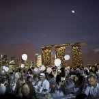 Guests sit at dinner tables set up with the Marina Bay Sands and the financial skyline as a backdrop, Singapore. Diner en Blanc or