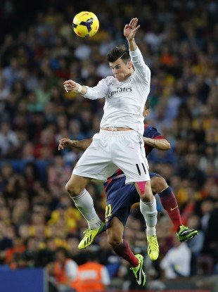 Real Madrid's Gareth Bale jumps for the ball with Barcelona's Adriano Correia.