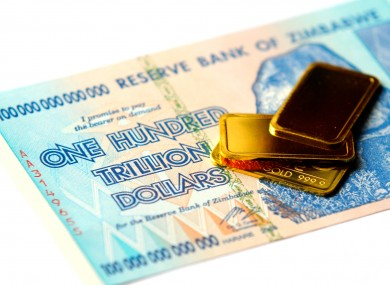 A Zimbabwe One Hundred Trillion Dollar note and small gold bars