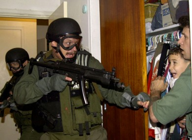 Elian Gonzalez is held by one of the two men who rescued him from the ocean as US government officials search the home in April 2000.