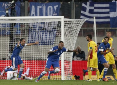 Greece's Kostas Mitroglou, center left, celebrates his second goal against Romania during a World Cup qualifying playoff first leg soccer match at the Karaiskaki stadium in the port of Piraeus.
