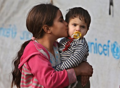 A Syrian displaced girl kisses her younger brother at one of the Syrian refugee camps at Delhamiyeh village in the Bekaa valley in Lebanon.