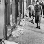A youth with a broom prepares to clear up the broken window glass from a Jewish shop in Berlin, the day after the Kristallnacht rampage.<span class=