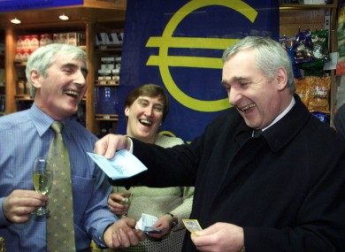 Then Taoiseach Bertie Ahern (right) celebrates the adoption of the Euro currency on the 1st of January 2002 with with Jim O'Neill and his wife Marian, proprietors of O'Neill's newsagents.