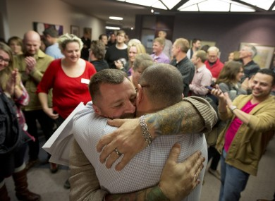 Chris Serrano, left, and Clifton Webb embrace after being married, as people wait in line to get licenses in Salt Lake City.