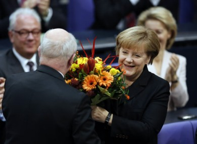German Chancellor Angela Merkel receives flowers from well-wishers this morning.