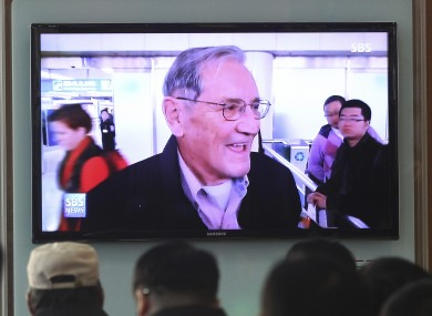 People watch a TV news programme showing Merrill Newman released by North Korea.