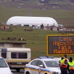 The now-completed dome is seen in the background as police stop cars from using the road running past Mandela's homestead.<span class=