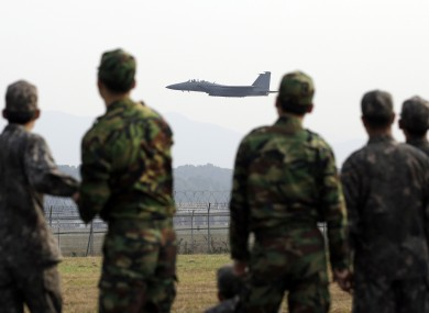A South Korean Air Force F-15K fighter flies as soldiers watch.