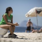 A woman sits on a toilet on Ipanema beach to protest water pollution in Rio de Janeiro, Brazil. Water pollution has become a hot-button issue because much of the city's sewage flows untreated into the city's waterways and with just over two years to go before the start of the 2016 Olympic games. <span class=