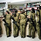 Military service is mandatory for all Israelis. Fifteen years after completing her own service, Israeli photographer Rachel Papo documents young female soldiers buying things at a military kiosk counter in 2004.<span class=