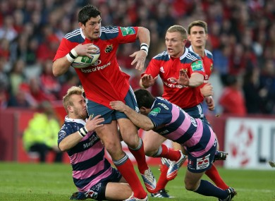 James Downey of Munster bursts through the tackles of Gloucester pair Dan Robson and Jonny Bentley.
