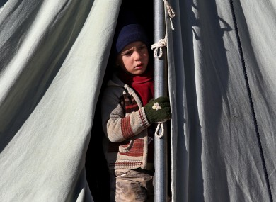A Syrian child looks out through his tent at a refugee camp in the eastern Lebanese border town of Arsal