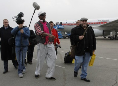 Rodman arriving at Pyongyang airport with his entourage, including Cooper (far left).