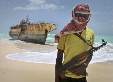 Masked Somali pirate 'Hassan' stands near a Taiwanese fishing vessel in this September 2012 file photo