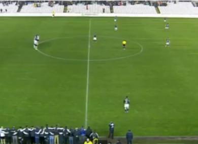 The players of Racing Santander stand motionless in the centre circle.