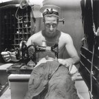 A Royal Navy sailor on board HMS Alcantara uses a portable sewing machine to repair a signal flag during a voyage to Sierra Leone in 1942.<span class=