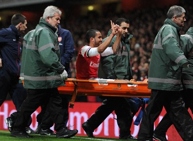 Walcott gestures to Spurs fans while being stretchered off.