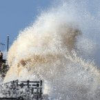 Waves crash over the sea wall at New Brighton, Wirral.<span class=