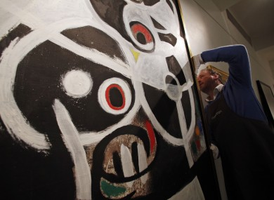An auction house worker adjusts Joan Miro's 1968 oil painting