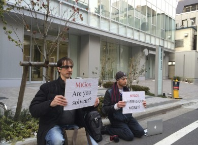 Two bitcoin traders hold protest signs as they conduct a sit-in in front of the office tower housing MtGox in Tokyo.