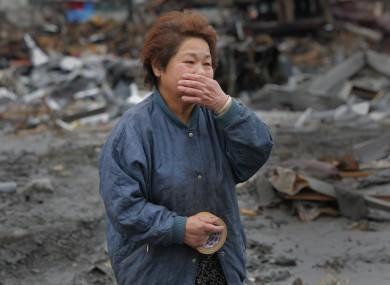 Reiko Miura, 68, cries as she looks for her sister's son at a tsunami-hit area in Otsuchi, Iwate Prefecture.