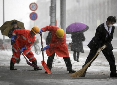 Railway station workers shove snow from the street in Yokohama, Japan.