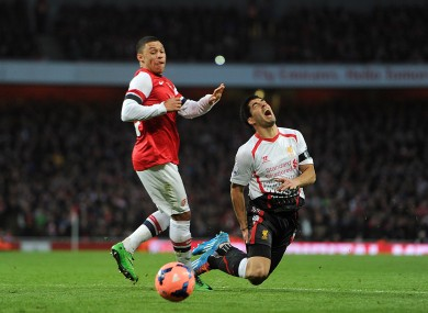 Liverpool's Luis Suarez goes to ground after a challenge from Arsenal's Alex Oxlade-Chamberlain.