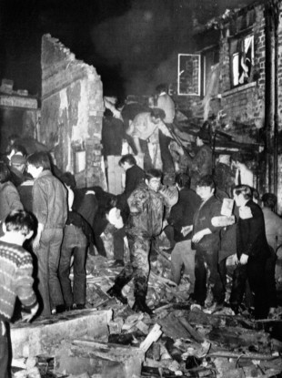 Rescuers dig with their bare hands in the rubble of McGurk's bar shortly after the bomb exploded.