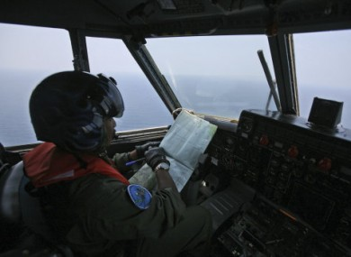 Indonesian Navy pilot checks his map during a search operation.
