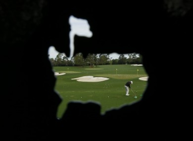In a photo taken through the cut out of a Masters' logo, Lucas Glover hits on the practice range today.