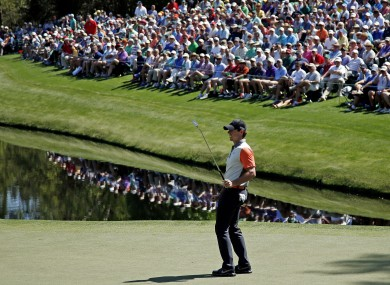 Rory McIlroy watches his putt on the 16th green during the first round of the Masters golf tournament yesterday.