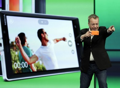 Stepen Elop, executive vice president of Nokia, demonstrates the picture taking ability of the new Nokia Lumia 930 phone during a keynote address of the Microsoft Build Conference.