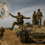 An Israeli soldier jumps off an armored vehicle as he celebrates with his unit their return from the Gaza Strip.<span class=