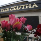 Flowers are laid at the Clutha bar in Glasgow, Scotland, four months after 10 people died following a helicopter accident.<span class=