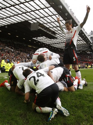 Liverpool triumphantly celebrate Luis Suarez' goal at Old Trafford.