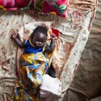 Baby Chol sleeps in the tent the UN mission in Rumbek has given his family, and roughly 90 other Nuers who have taken up shelter in the site. Photo: Mackenzie Knowles Coursin/Oxfam<span class=