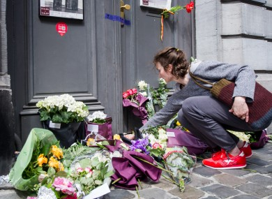 A woman lays flowers at the Jewish Museum.